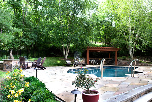 Artistic Tree & Landscape Creations hardscape services — modern home outdoor stone patio with pool and pergola