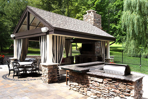 Artistic Tree & Landscape Creations hardscape services — modern home outdoor kitchen with stone patio and pergola, stone retaining wall and fireplace