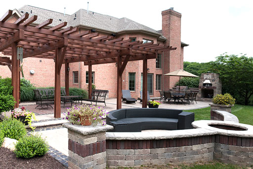 Artistic Tree & Landscape Creations hardscape services — modern home outdoor space with pergola, pizza oven, block retaining wall and fire pit