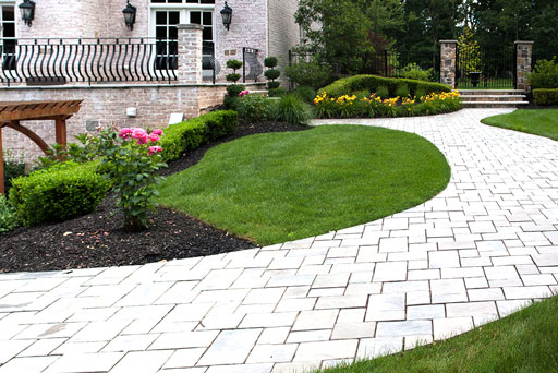 Artistic Tree & Landscape Creations hardscape services — modern home outdoor paver stone walkway