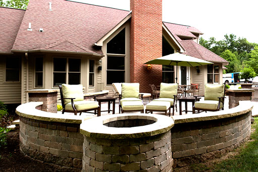 Artistic Tree & Landscape Creations hardscape services — modern home outdoor space with block retaining wall and fire pit