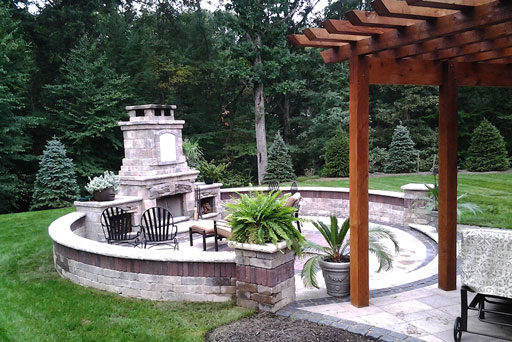 Artistic Tree & Landscape Creations hardscape services — modern home outdoor oasis with stone patio, retaining wall and fireplace pizza oven