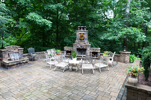 Artistic Tree & Landscape Creations hardscape services — modern home outdoor space with stone patio, water feature and fireplace