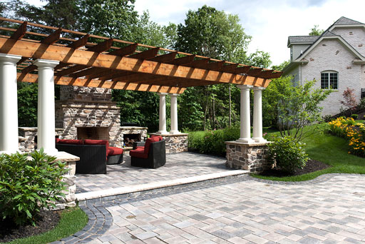Artistic Tree & Landscape Creations hardscape services — modern home outdoor lounge with pergola, stone patio and fireplace