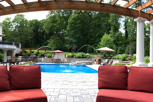 Artistic Tree & Landscape Creations hardscape services — modern home outdoor pool with stone patio and pergola
