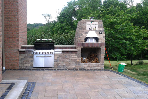 Artistic Tree & Landscape Creations hardscape services — modern home outdoor kitchen with stone pizza oven and patio