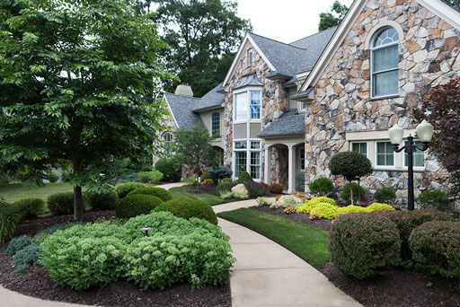 Artistic Tree & Landscape Creations residential landscape service — modern home and walkway