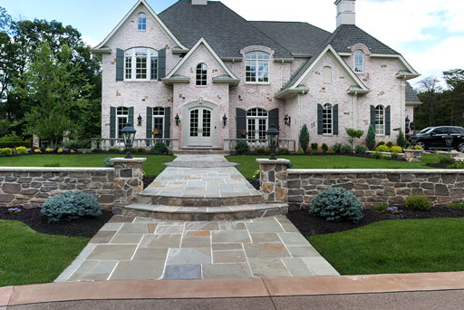 Artistic Tree & Landscape Creations residential landscape service — modern home and stone walkway
