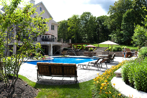 Artistic Tree & Landscape Creations residential landscape service — modern home, stone patio, pool